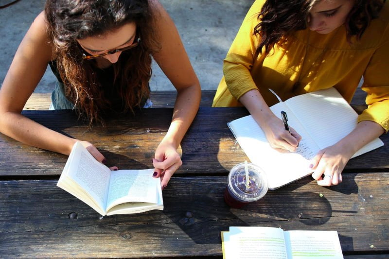1 woman reading next to another person writing
