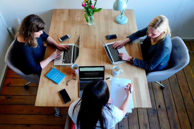 3 women sitting together at a table with laptops