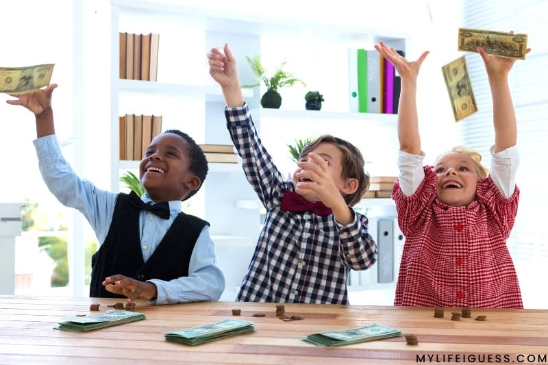 3 children laughing and throwing money into the air