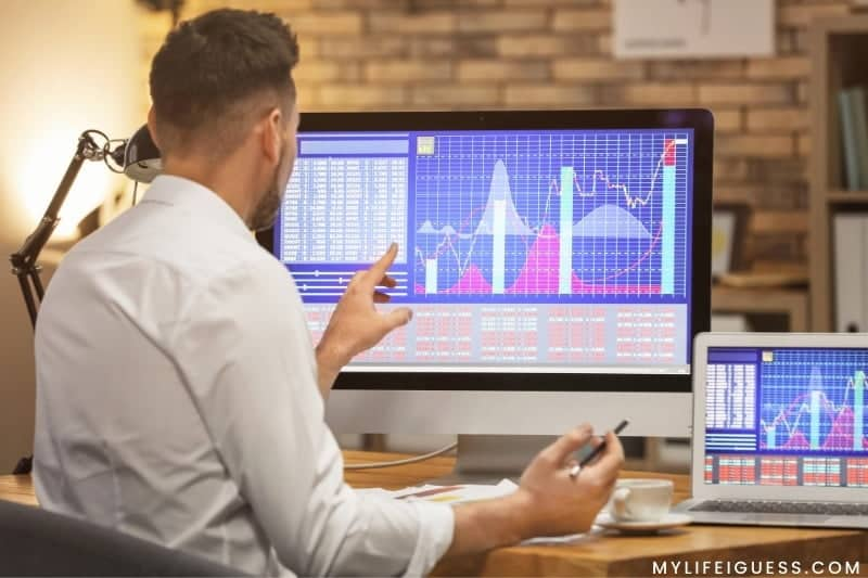 man looking at stock performance on his computer screen