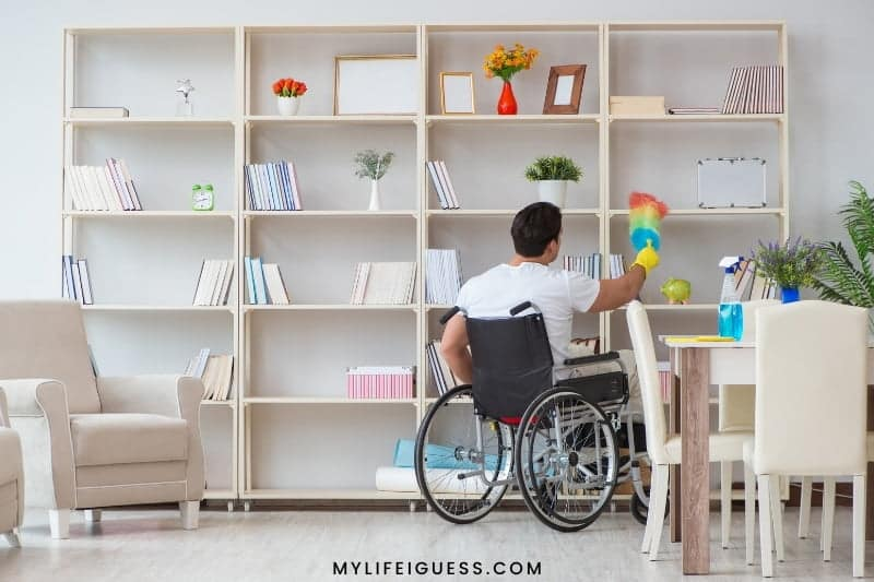 man in wheelchair dusting his apartment
