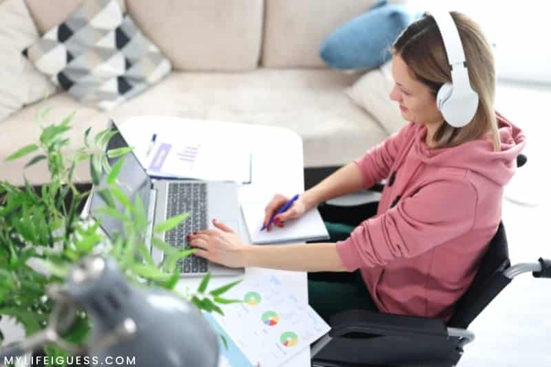 young woman working at a desk with the text Are You Ready to Be Your Own Boss? 10 Things To Consider