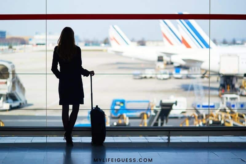 silhouette of a women with a suitcase at an airport