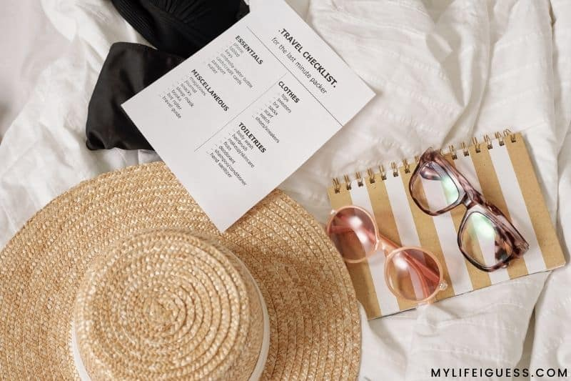 a travel checklist and other vacation items laid out on a bed